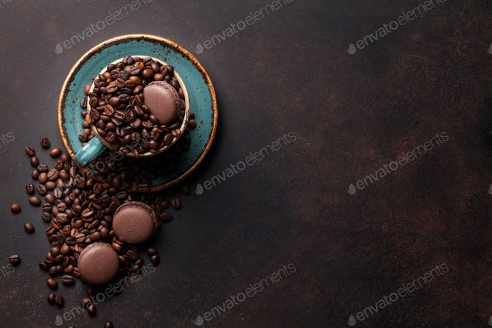 Coffee cup with roasted beans and macaroons