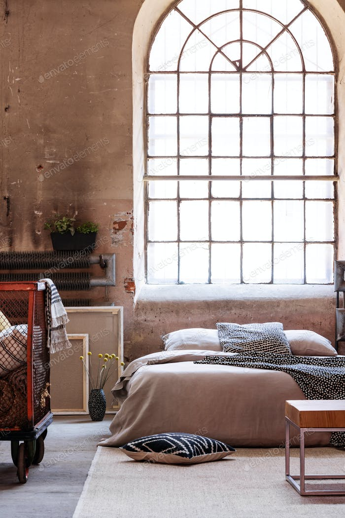 Real photo of an industrial bedroom interior with a big window a