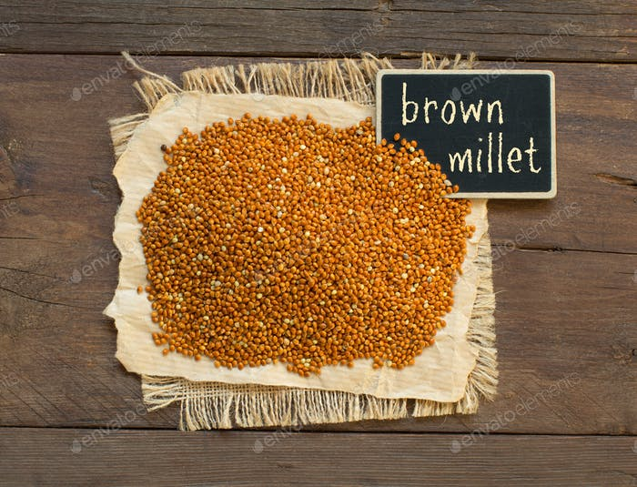 Whole brown millet pile with a small chalkboard