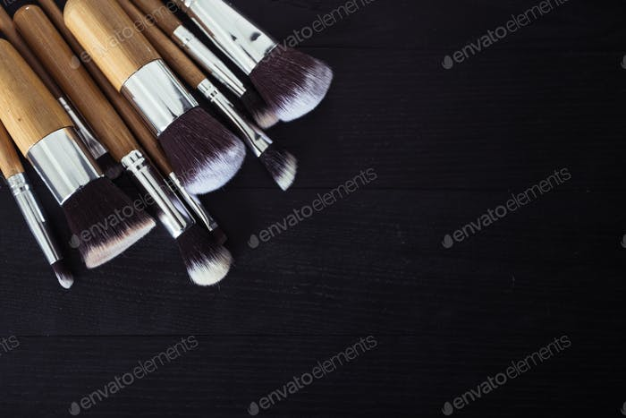 make up brushes with powder and rouge on a black wooden backgroud