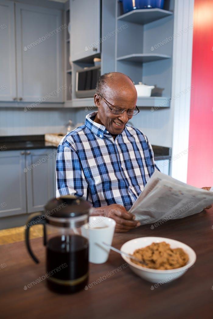 Lächelnder Mann Zeitung lesen während mit Frühstück