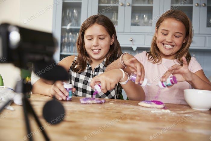 Two girls video blogging in kitchen preparing ingredients