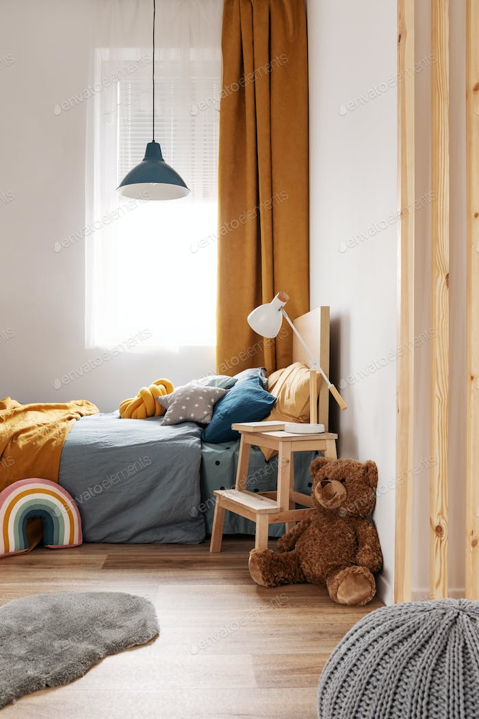Stylish blue and orange kid's bedroom design in bright apartment