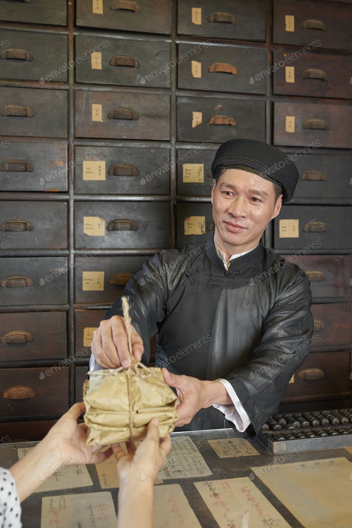 Chinese medicine practitioner giving packages