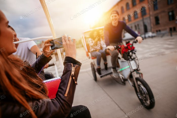 Woman photographing friends on tricycle ride.
