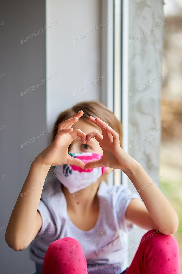Little girl, child in mask making hearts from hands, coronavirus quarantine