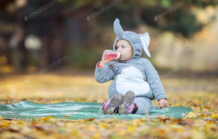 Little girl in elephant costume drinking beverage in park