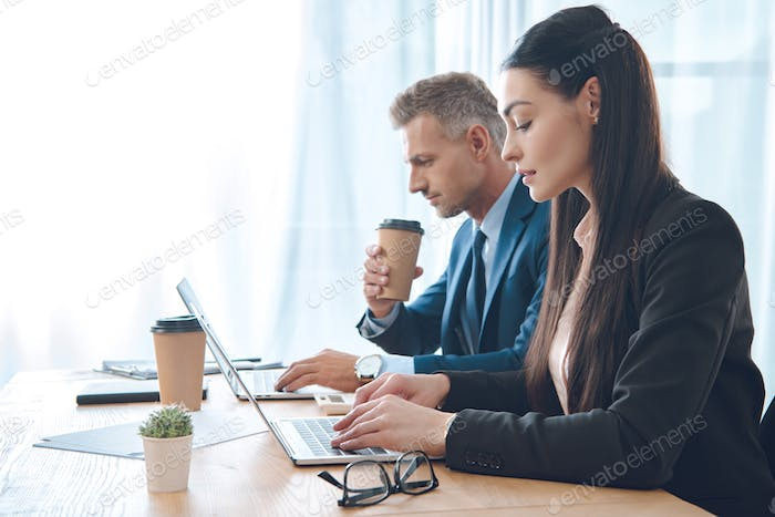 side view of businesspeople working at workplace with laptop in office