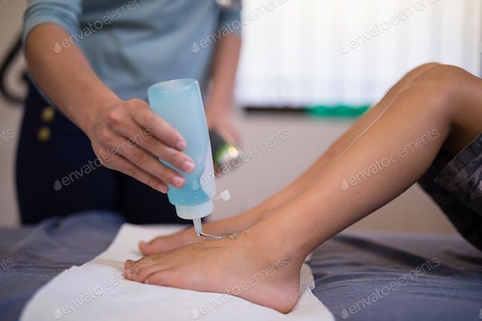 Weibliche Therapeutin Gießen Scan-Gel auf die Füße des Jungen