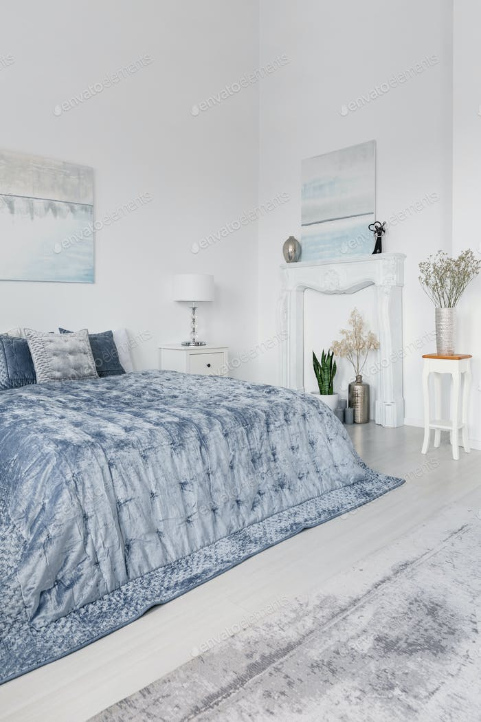 Posters and plants in white simple bedroom interior with blue be