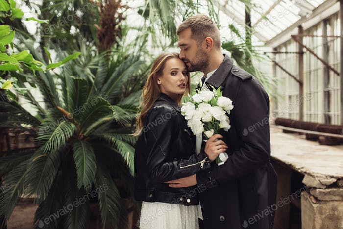 Young beautiful woman in black leather jacket and white dress wi
