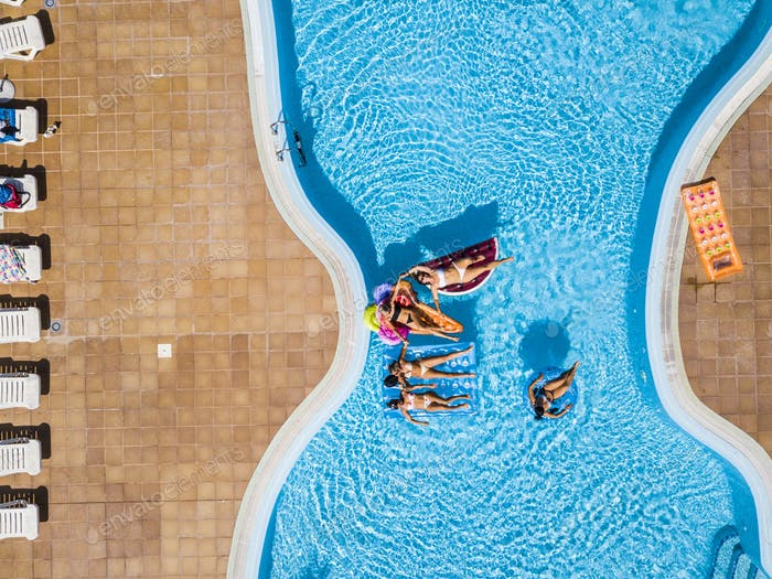 Aerial vertical view of group of women friends at the pool