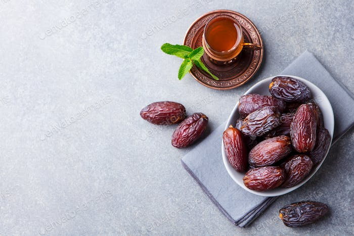 Fresh Medjool Dates in a bowl with tea. Ramadan kareem. Grey stone background. Top view. Copy space