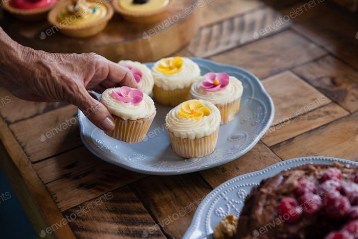 Abgeschnittenes Bild von Senior Frau halten Cupcake am Tisch