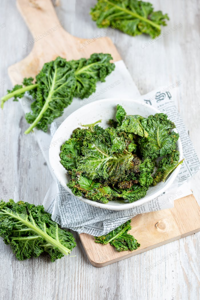 Homemade Green Kale Chips on vintage newspapper, white background.