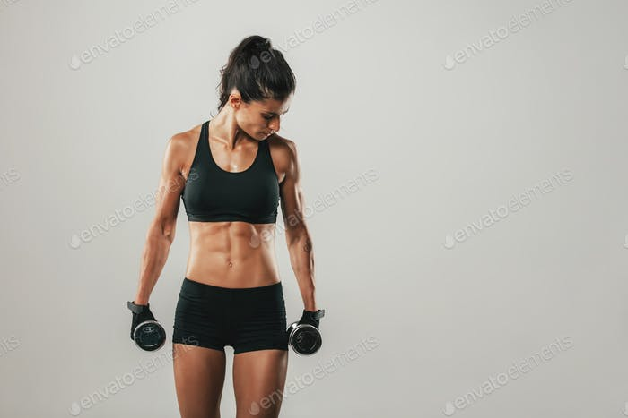 Attractive woman holding dumbbells facing sideways