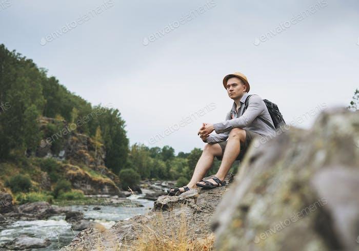 Joven viajero en sombrero de paja con mochila en río montaña