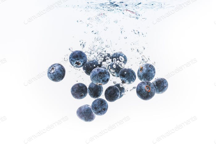 Organic Blueberries dropped into clear water