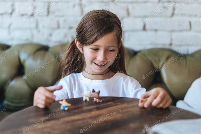 Girl playing with small figures sitting on soft