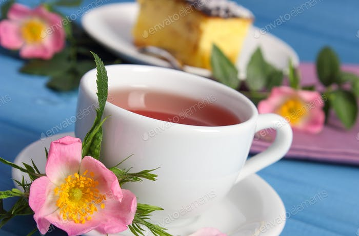 Hot tea with cheesecake and wild rose flower on boards