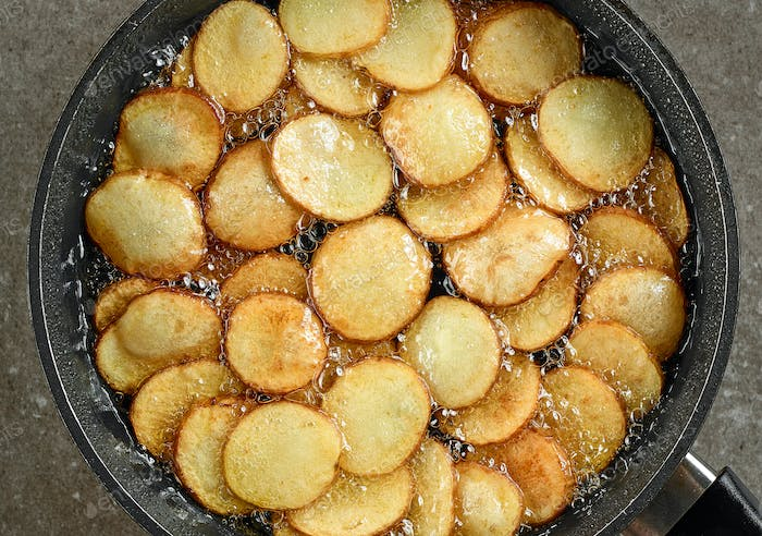 frying potatoes in pan with oil