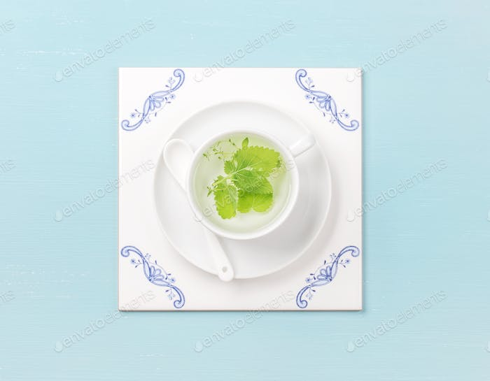 Cup of tea on white tile board over sky-blue background