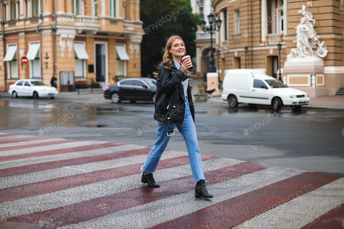 Young smiling woman in leather jacket and jeans joyfully looking