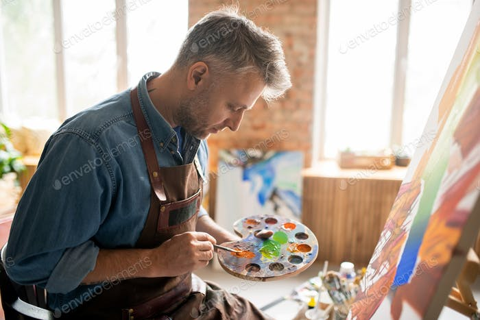 Creative man in apron mixing colors on palette in front of easel in studio