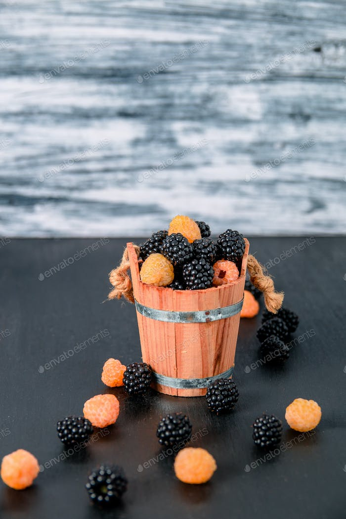 Black and yellow raspberries in a wooden basket on grey  background. Close up.