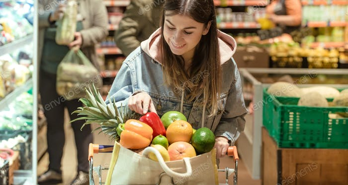 A young woman buys groceries in a supermarket.