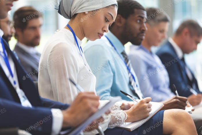 Side view of young mixed race businesswoman writing on notepad during seminar in office building