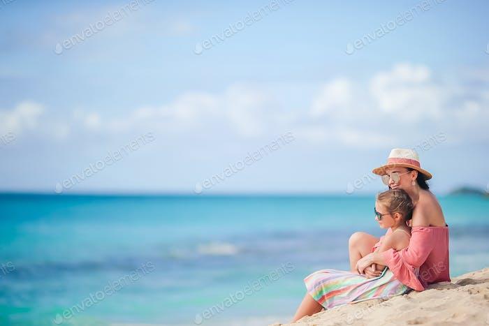 Kleine niedliche Mädchen und junge Mutter am tropischen Strand
