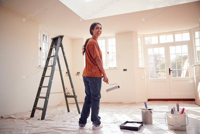 Rear View Of Woman With Paint Roller Decorating New Home
