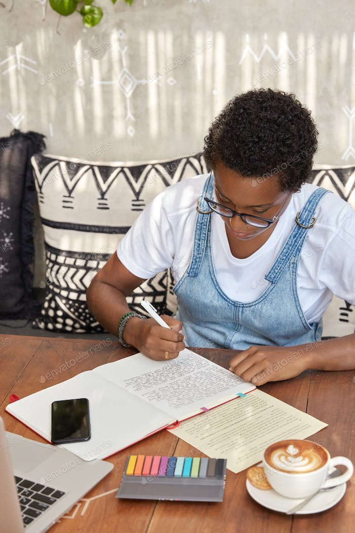 African American student makes translation exercises, rewrites sentences in notebook, drinks aromati
