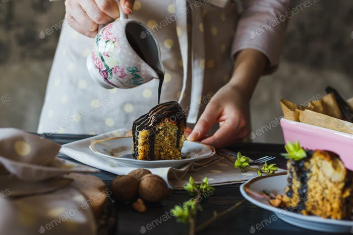 Close-up of the hand of baking girl is pouring chocolate glaze over a mouth-watering piece of cake.