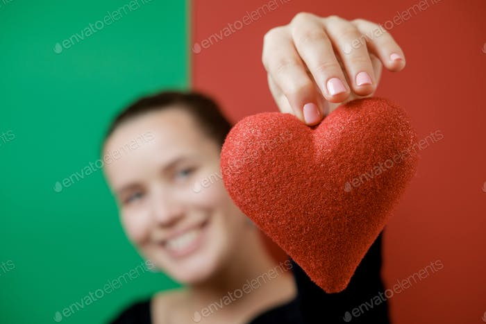 Pretty young woman with a red heart on red and green background. Valentine's Day