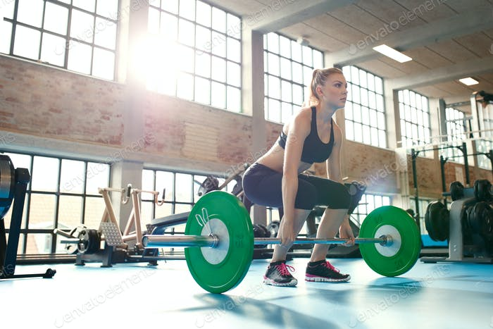 Focused young woman lifting weights in a gym