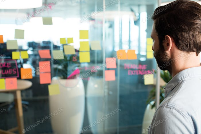Close up of businessman looking at adhesive notes and strategy on glass