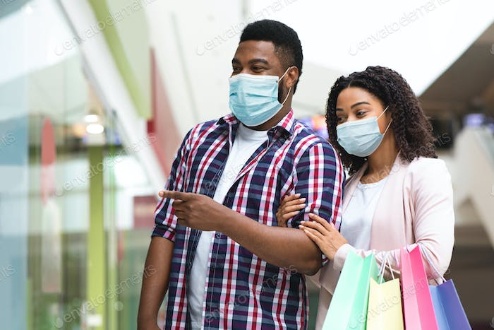 Pandemic Shopping. African Couple With Medical Masks On Face Walking In Mall