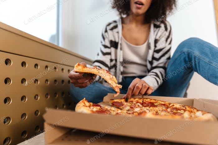Pretty young african woman indoors at home eat pizza.