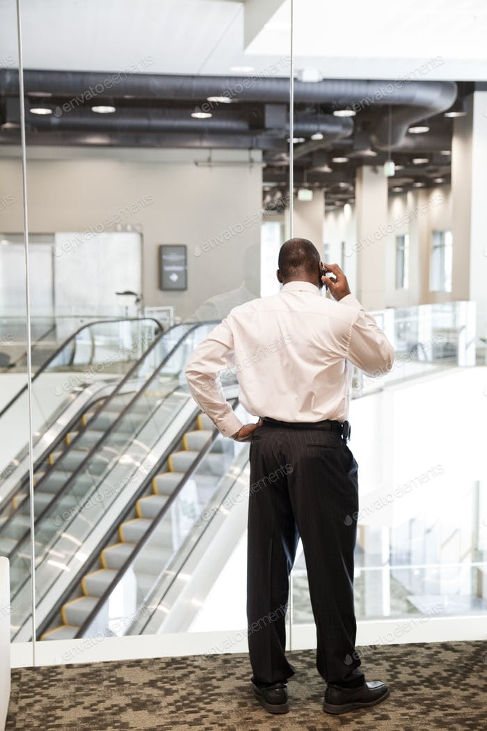 Black businessman on the phone in a large business center lobby.