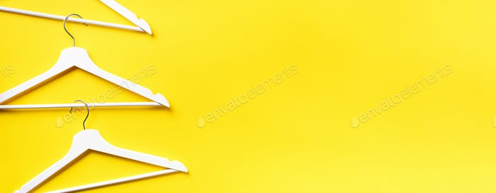 Top view of white clothes hangers on yellow background with copy space. Flat lay. Minimalism style