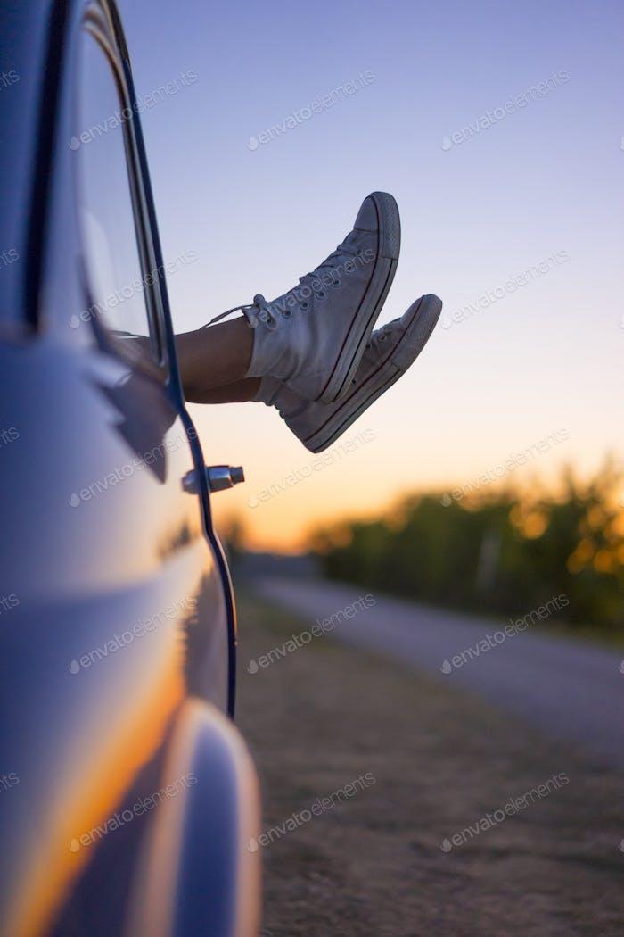 jóvenes mujer pies fuera de de vintage coche ventana