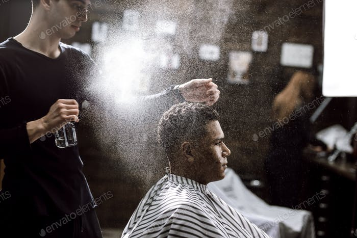 The barber dressed in a black clothes is doing the hair styling to the stylish black-haired man