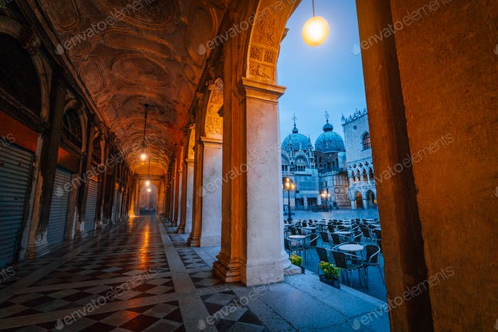 Evening view of Basilica di San Marco and Campanile through the street arch hallway on San Marco in