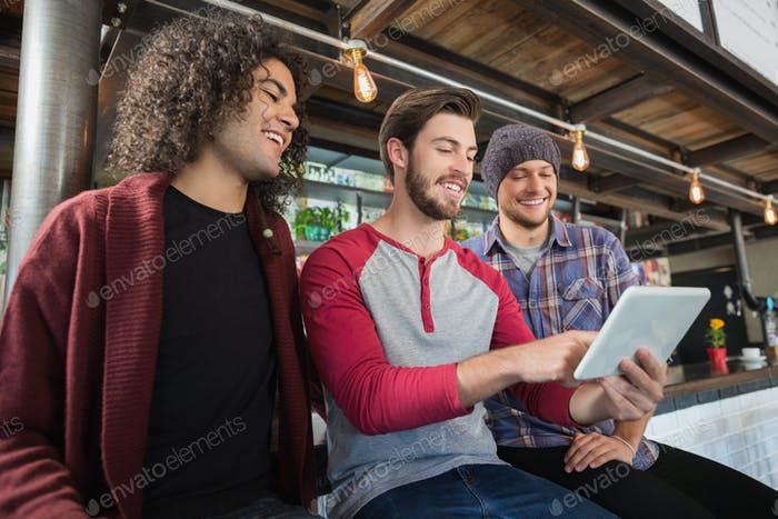 Happy male friends using digital tablet in restaurant