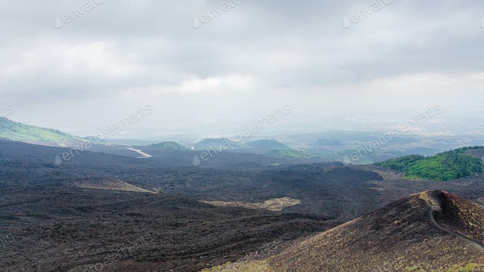 clouds over black lava field on Mount Etna