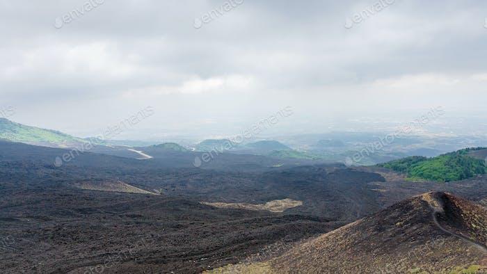 Wolken über schwarzem Lavafeld auf dem Ätna
