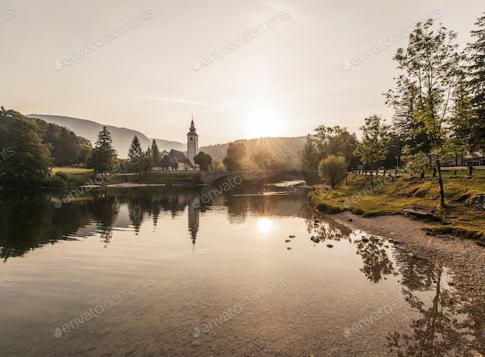 Wunderschöne Waldreflexion im Bohinj-See mit umliegenden Bergen