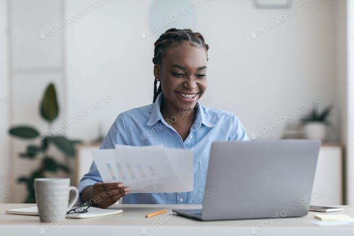 Papierkram. Fröhliche schwarze Millennial Geschäftsfrau, die mit Laptop und Dokumenten im Büro arbeitet